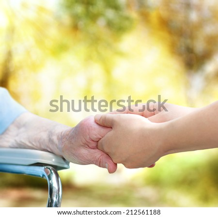 Elderly woman in wheel chair holding hands with young caretaker in autumn - stock photo