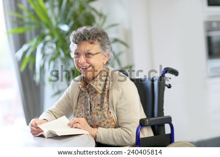 Elderly woman in wheelchair reading book - stock photo