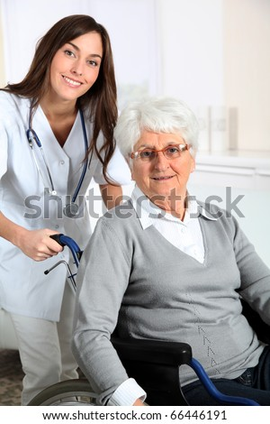 Elderly woman in wheelchair with nurse at home - stock photo