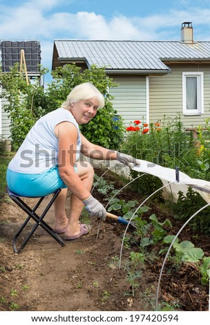 Elderly woman is engaged in weeding in the garden, sitting on a chair - stock photo