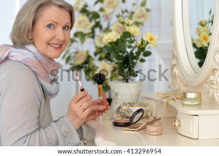 elderly woman is painted before a mirror and smiling - stock photo