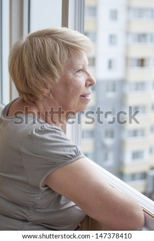 Elderly woman look out the window - stock photo