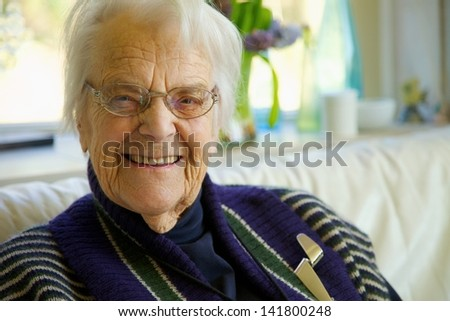 Elderly woman looking at the camera and smiling - stock photo