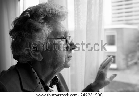 Elderly woman looking out a window