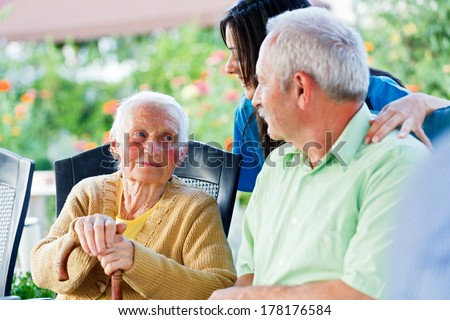 Elderly woman looking to the carer and her son, the visitor.  - stock photo