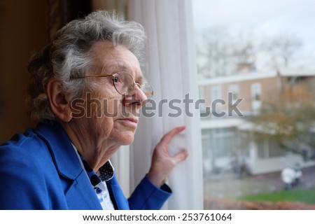 Elderly woman looks out a window - stock photo
