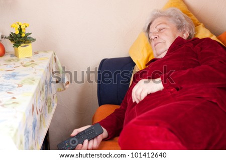 Elderly woman lying on the couch with remote in hand and sleeps