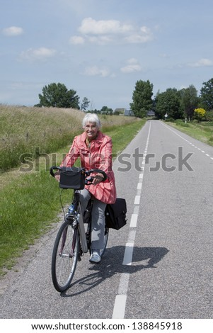 Elderly woman on a bicycle in a Dutch polder - stock photo