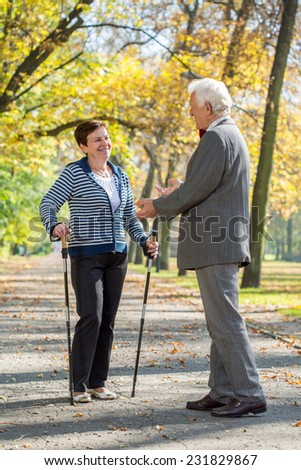 Elderly woman on nordic walking meeting her old friend