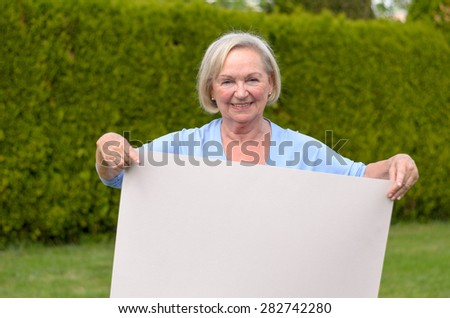 Elderly woman outdoors and looking at camera while showing a blank whiteboard for advertising or the message of an awareness campaign - stock photo