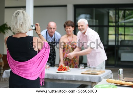 Elderly woman photographing a group of senior - stock photo