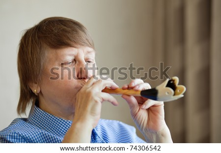 Elderly woman playing a wind instrument at home