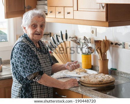 Elderly woman preparing croquettes at home - stock photo