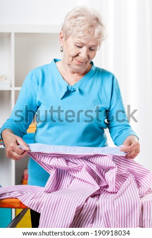Elderly woman preparing striped shirt to ironing - stock photo