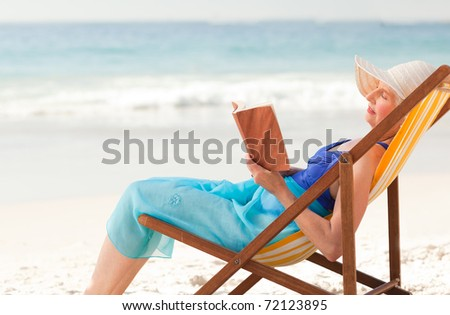 Elderly woman reading a book at the beach - stock photo