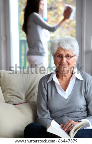 Elderly woman reading book while housekeeper cleans windows - stock photo