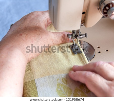 elderly woman sewing on the sewing machine - stock photo