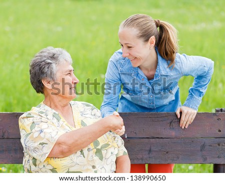 Elderly woman shaking hand with her carer - stock photo