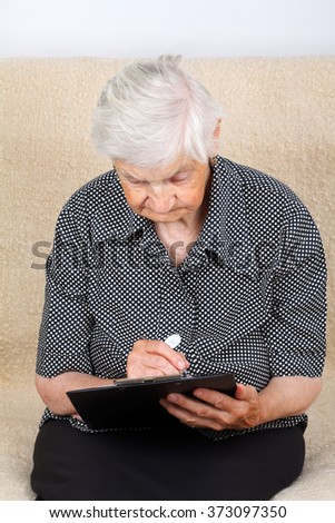 Elderly woman signing on the contract - stock photo