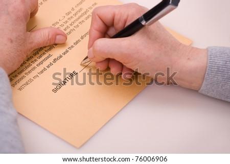 elderly woman signing testament - stock photo