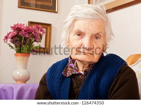 Elderly woman sits on the bed - stock photo