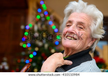Elderly woman sitting and smiling near a christmas tree