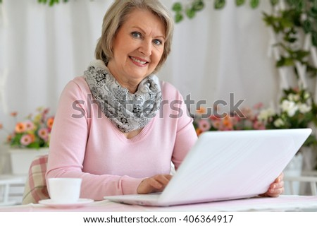elderly woman sitting at the computer with a cup