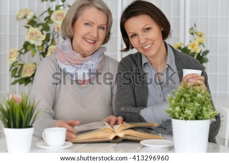 elderly woman sitting at the table with her daughter and reading a book - stock photo