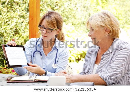 Elderly woman sitting in the garden with home health care nurse and consulting. Middle age caregiver holding in hand digital tablet with blank screen and giving advice to her patient.  - stock photo