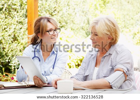Elderly woman sitting in the garden with home health care nurse and consulting. Middle age caregiver holding in hand digital tablet and giving advice to her patient.  - stock photo