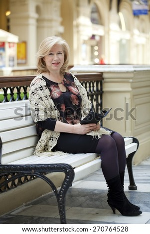 Elderly woman sitting on a bench in the mall with pad
