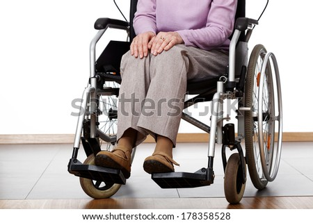 Elderly woman sitting on a wheelchair in home - stock photo