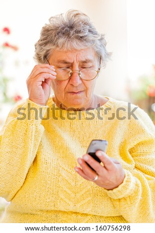 Elderly woman sitting on the veranda and waiting for a call  - stock photo