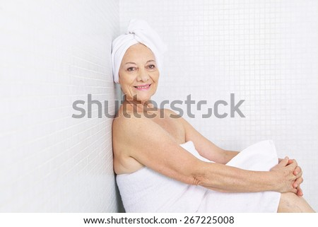 Elderly woman sitting releaxed in a relaxation room in spa - stock photo