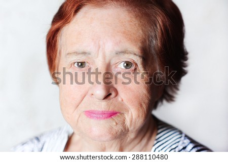 Elderly woman smiling indoors. Looking at camera. Senior female. - stock photo