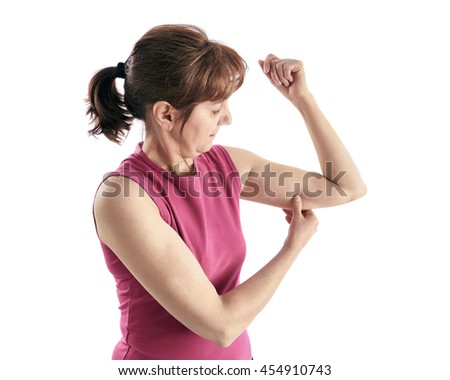 Elderly woman stretches the skin underarm, on a white background.
