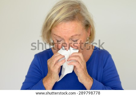 Elderly woman suffering from a seasonal cold or hay fever blowing her nose on a handkerchief over a grey background