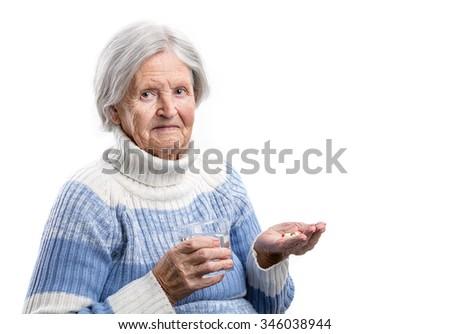 Elderly woman taking her medication over white  - stock photo