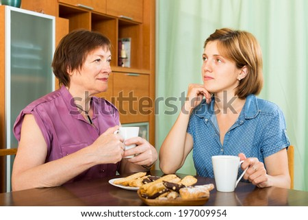 Elderly woman talking with her young daughter and during tea-drinking - stock photo