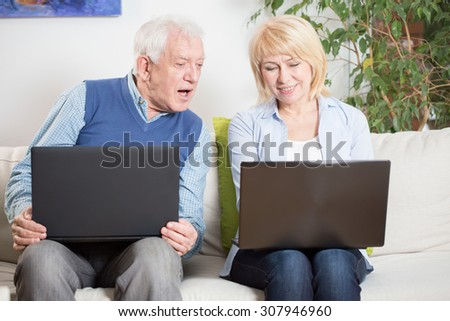 Elderly woman teaching her surprised husband using laptop - stock photo