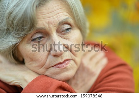 elderly woman thinking about something in the fresh air - stock photo