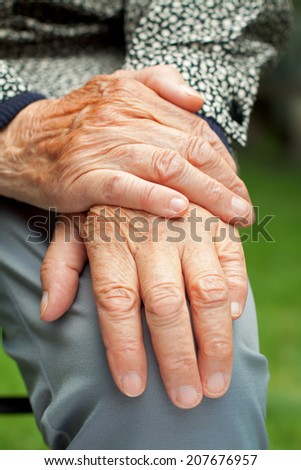 Elderly woman touch her wrinkled hand