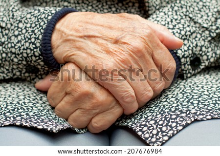 Elderly woman touch her wrinkled hand - stock photo