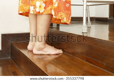 Elderly woman up stairs with walker at home. - stock photo