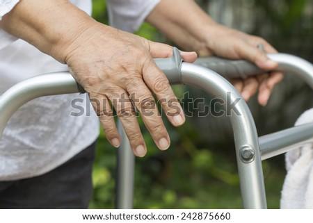 Elderly woman using a walker  - stock photo