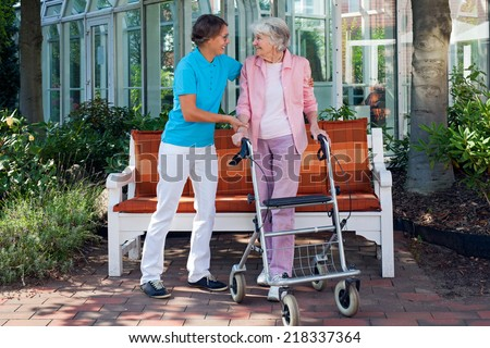 Elderly woman using a walking aid with the help of her loving daughter or care assistant enjoying a day in the park with a glass conservatory in the background - stock photo