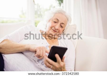 Elderly woman using her smartphone lying on sofa - stock photo
