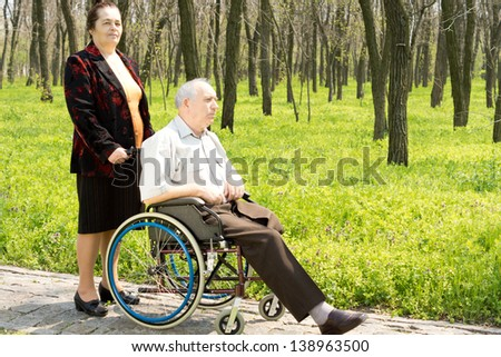 Elderly woman walking her husband, who has had one leg amputated above the knee, in his wheelchair along a rural path in woodland