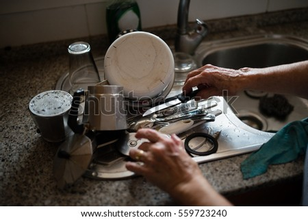 Elderly woman washing dishes at home