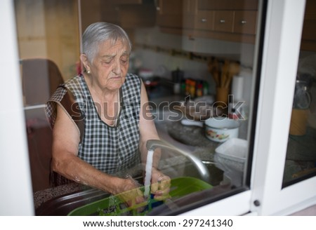 Elderly woman washing dishes in the kitchen - stock photo